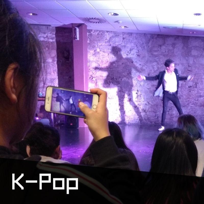 Exhibició de K-Pop, ballarí i noia jove amb mòbil fent les fotos de la performance