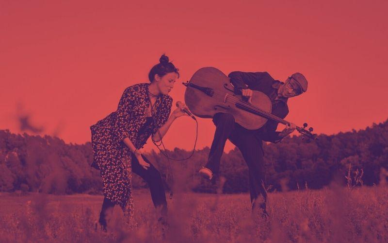 Nihan Devecioglu i Sasha Agranov tocant i cantant a un paisatge rural.