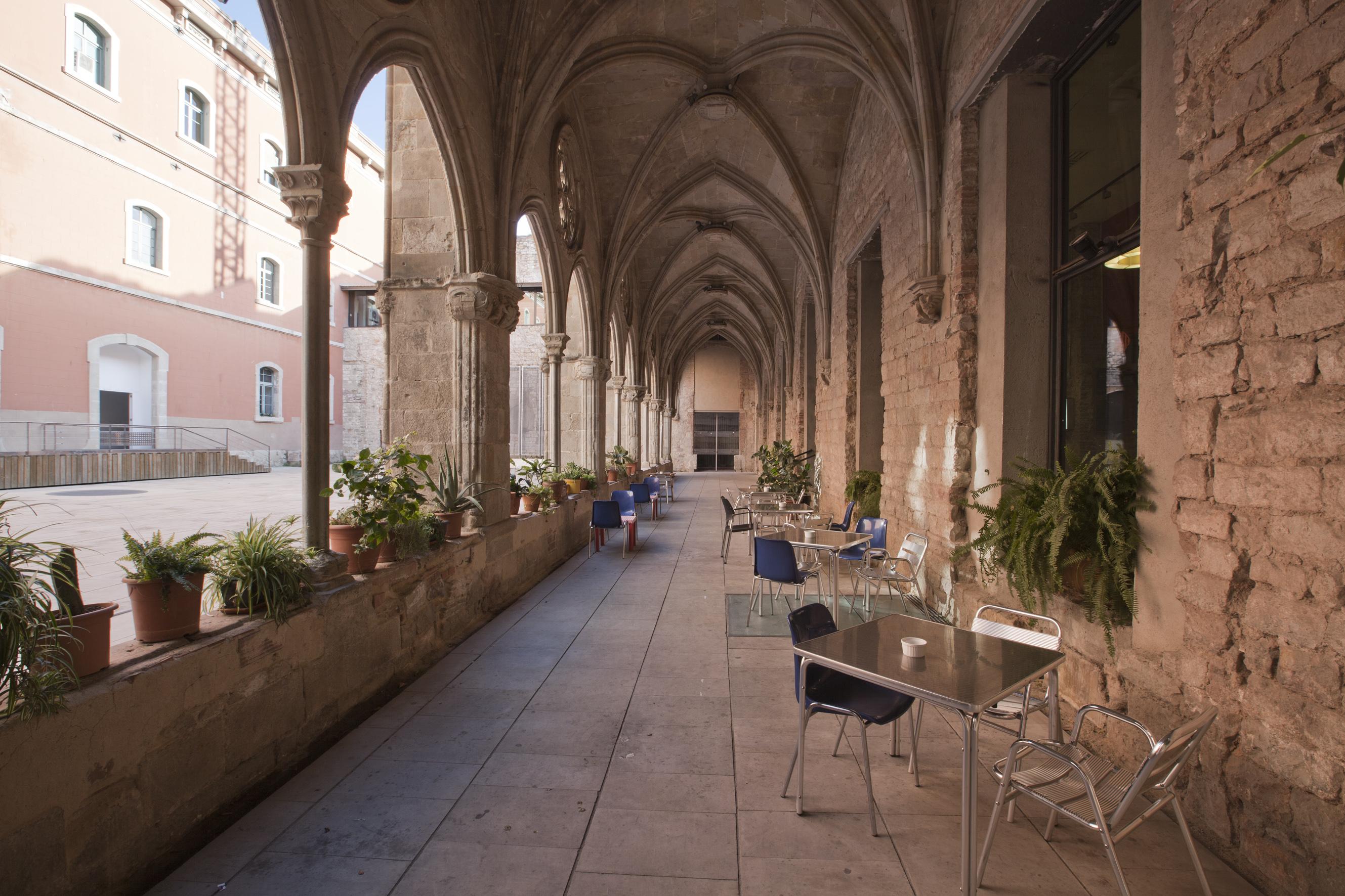 Imatge dels porxos laterals del claustre del Convent i les taules del bar del Convent. Fotografia realitzada per Mireia Plans.