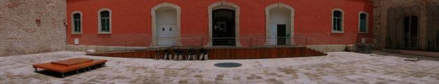 Vista panoràmica del claustre del convent amb un escenari preparat per una actuació, amb la perspectiva de la part interior del carrer comerç