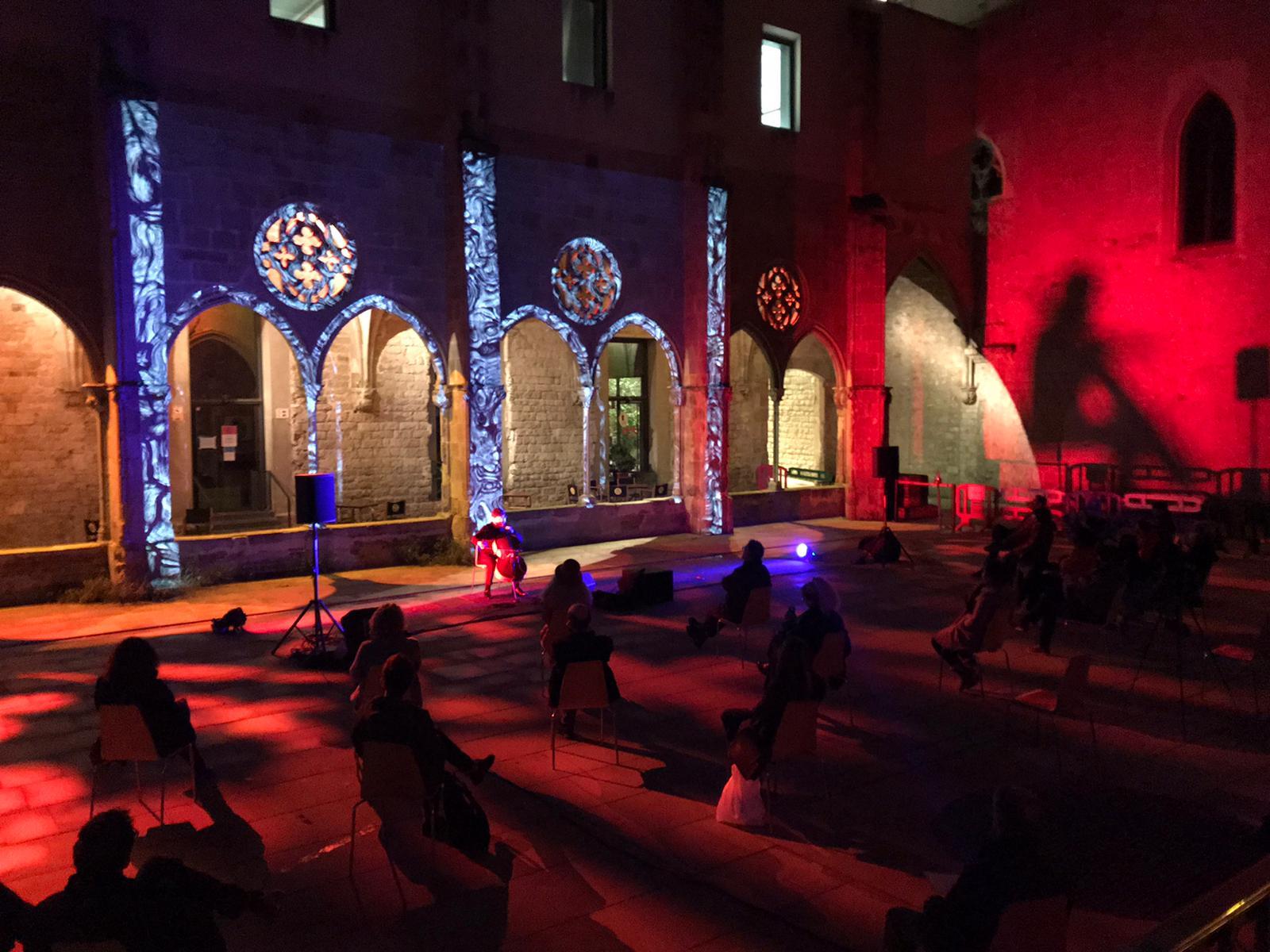 Vista del claustre del convent amb les projeccions mapejades a la façana d'estil gòtic, el públic i el músic Ivan Lorenzana