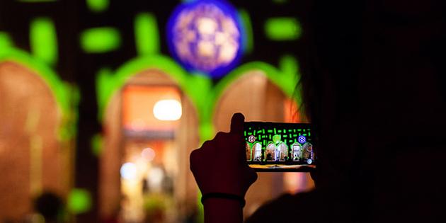Persona amb mòbil fent una foto del claustre del convent il·luminat amb el mapping