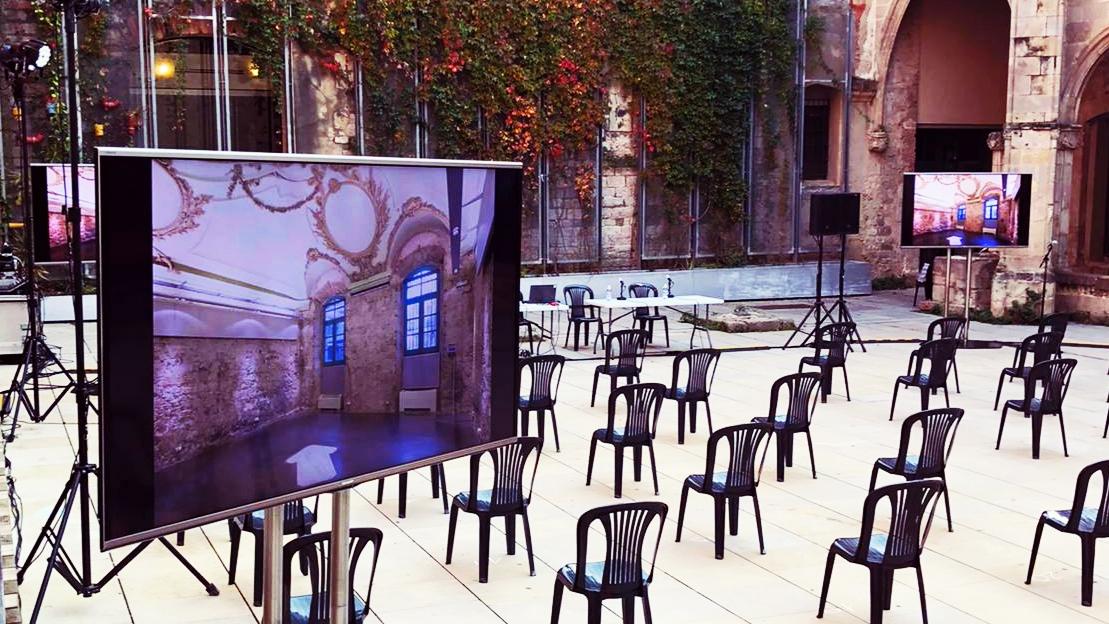 Imatge del claustre del convent amb cadires muntades a distància de seguretat i pantalles col·locades per a retransmetre el consell de barri.