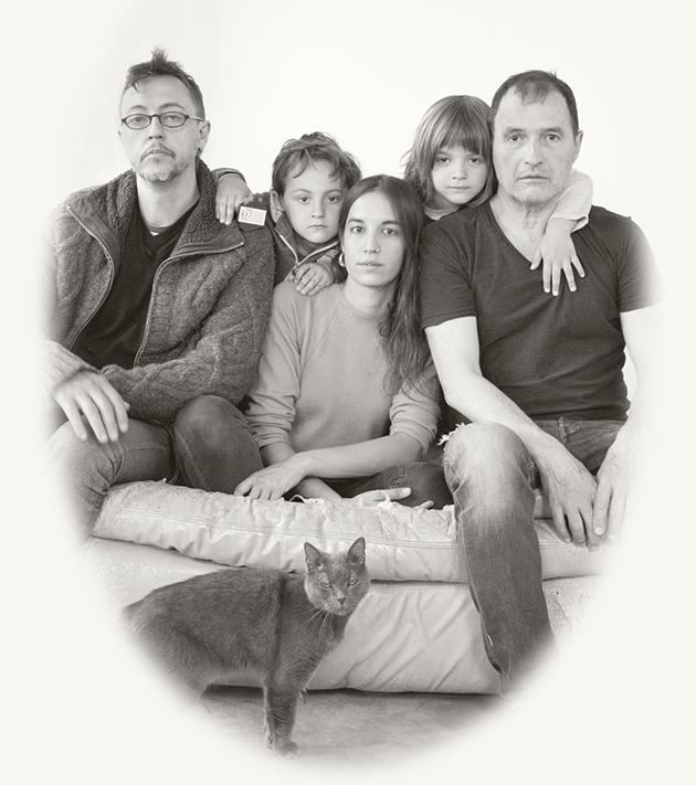 """Retrat realitzat amb estètica de fotografia antiga, d'una de les famílies no """"heteronormatives"""" amb tres persones adultes i dos infants."""